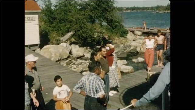 1950s: View of shack on island, pan to water. Views of people on dock. Man on dock. Tracking shot from boat, view of island. People eating on boat.