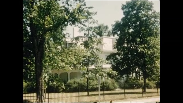 1950s: Exterior of house. View of street corner. Views of house. Closer pan across front of house.