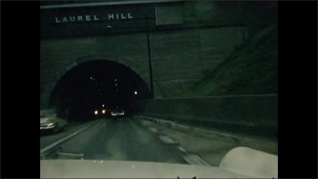 1950s: Tracking shots from car, driving down highway. Approaching tunnel. Driving through tunnel. Driving on highway.