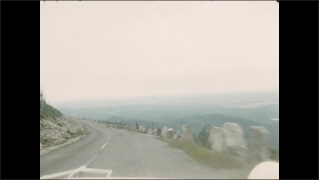 1950s: Driving through mountain pass. Driving down highway in mountains. Forest and trees.