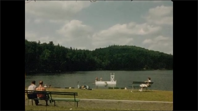 1950s: Driving down freeway road. Driving down forested road. People sit on benches and hang out around lake at park.