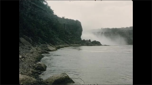 1950s: Waterfalls over cliff and into river. Boat crosses river.