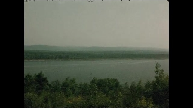 1950s: CANADA AND UNITED STATES: car parked by road. View across river from above. Car drives along rural road. Road sign