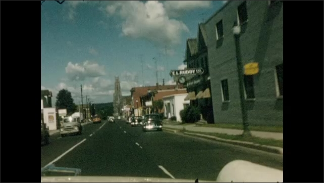 1950s: CANADA AND UNITED STATES: view along countryside road from window of car. Car drives through woods. Car drives through street in town. Flags hang in town