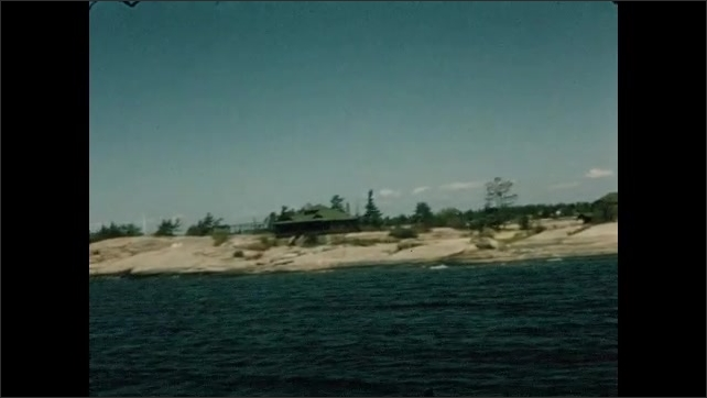 1950s: Tracking shots from boat, view of shoreline. View of water and shore from back of boat.
