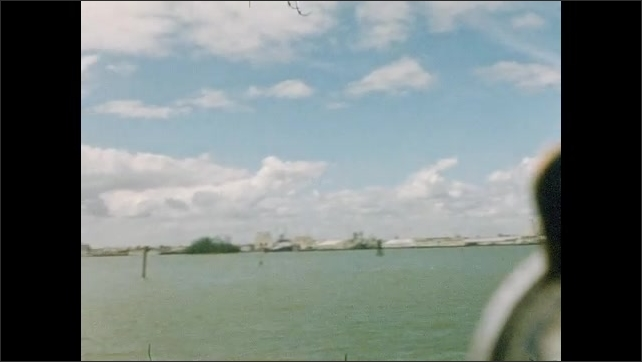 1950s: UNITED STATES: view of beach from water. Ship in harbor. Trees by beach. Marker buoy seen from boat.