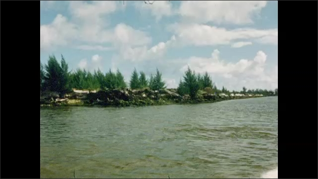1950s: UNITED STATES: boats on waterway. Yachts on water. Rocks and trees by shore. Boats on mooring