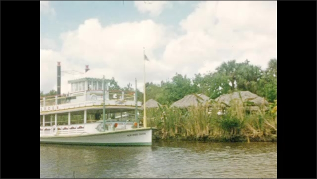 1950s: UNITED STATES: house and gardens by water. Palm trees by house. Luxury homes by water. Steam paddle boat. Mangrove swamps.