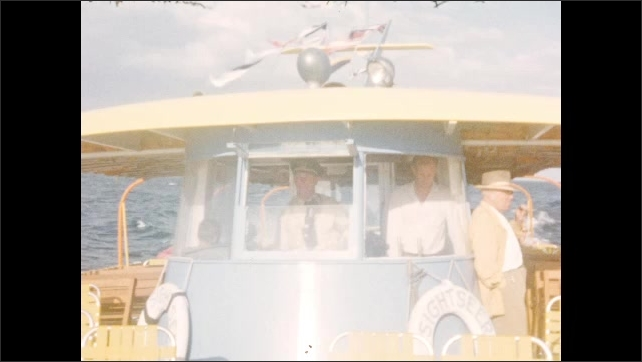 1950s: People on boat in ocean go passed buoy. Pilot in cabin of boat, while man stands next to cabin. View out rear of boat. Crane in brush. Sign for fair.