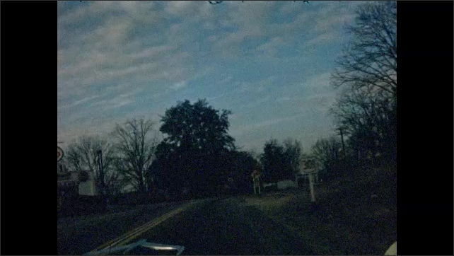 1950s: UNITED STATES: daytime view from car windscreen. Night time view from car windscreen. Dawn or dusk view.