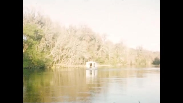 1950s: UNITED STATES: boat on waterway. Boat house on water. Trees by water. Reflection of trees in water