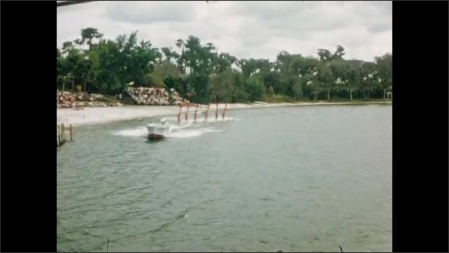 1950s: UNITED STATES: water ski display team. Performers on water skis behind boat. Water skiers carry flags.