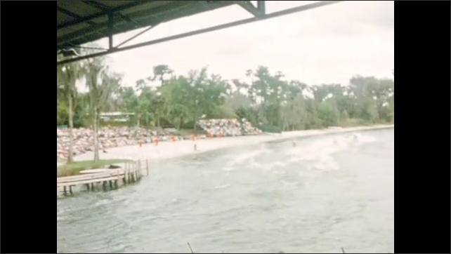 1950s: UNITED STATES: crowd watch water ski show on lake at Cypress Gardens. Boat on lake. Skiers balance on one leg behind boat