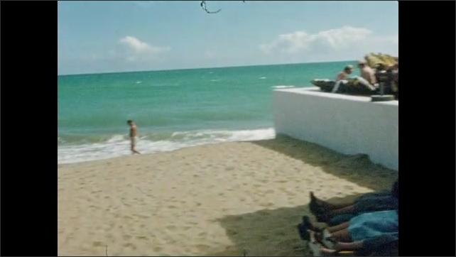 1950s: Yard.  Flowers.  Beach.  People lay in shade.  Tents.  People walk along.