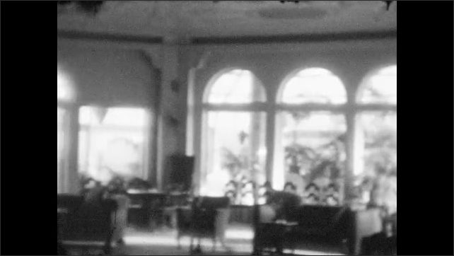1920s: girl runs around  and swaps seats in chairs near palms in planters and large windows in sunroom and resort hotel lobby.