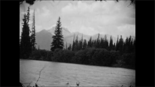 1920s: cars drive down road in small town near Canadian Rockies. river flows past forest and mountain range.