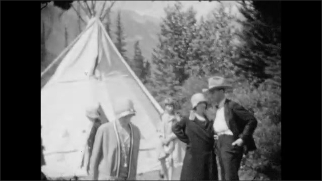 1920s: men and women step off observation boat with flag of Great Britain onto wood dock near water. people in hats and coats visit teepee in woods at edge of river.