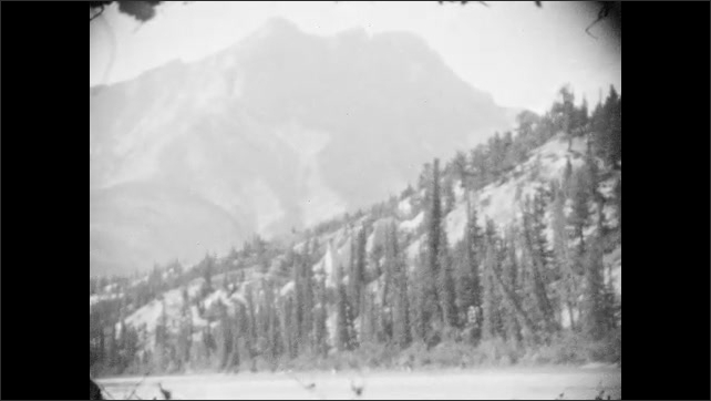 1920s: hills and mountains of Canadian Rockies surround lakes and streams of forests in Waterton Lakes Park, Canada.
