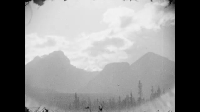 1920s: clouds soar above Canadian Rockies mountain range with trees and forests. Telephone poles stand near highway.