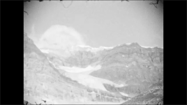1920s: snow sits on top of mountain peaks in Canadian Rockies. Men and women sit on horses in field near mountains and forest.