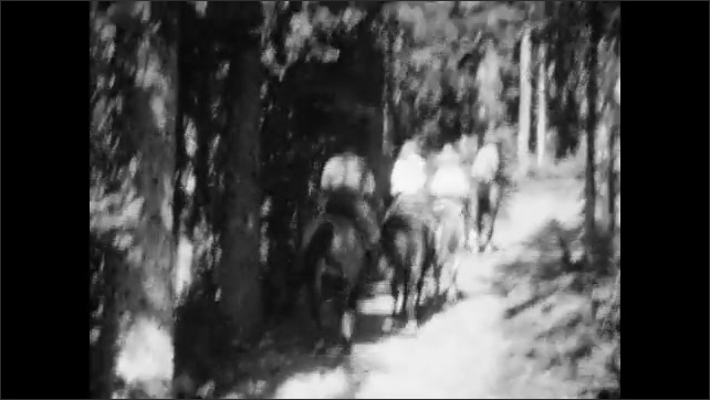 1920s: View from top of horse of three people who ride on horses on a path next to a house and a lake in the mountains. People ride horses on a trail surrounded by trees.