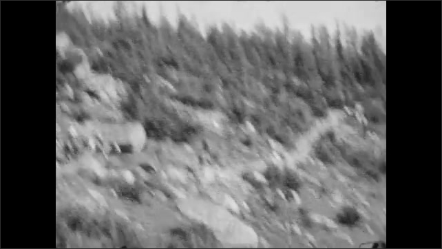 1920s: Lake at the bottom of mountains. View from top of horse of people who ride on horses on a rocky trail with trees. Yoho valley, lake at the bottom with a small town surrounded by mountains.