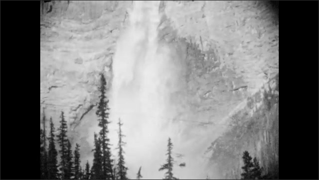 1920s: A child and woman stand next to water, waterfall in background. Takkakaw Falls.