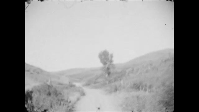 1920s: Moving on a dirt road next to hill with fence. Moving past tree next to fence. Moving on a curve next to a rocky wall.