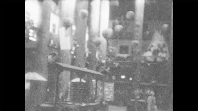 1920s: Woman standing near camera, man walking in background stops. Dark view inside building. Woman walking outside toward camera.