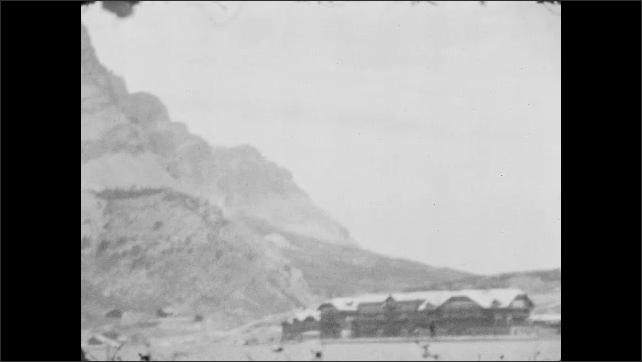 1920s: Mountain slopes and pines on lakeshore. Large lodge and water tower on edge of lake. Pine trees and mountains.