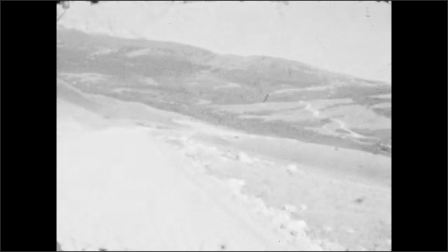 1920s: Car drives on winding mountain road. Mountain valley vista.
