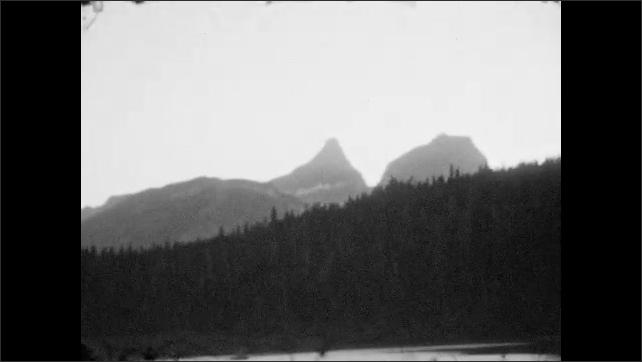 1920s: Mountain lake vista. Craggy mountain looms over lake.