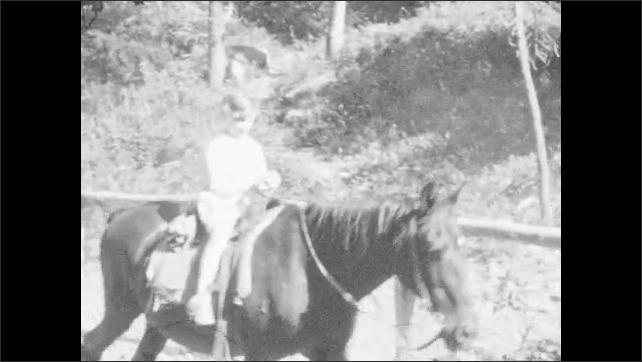 1920s: Men, women and children ride horses along mountain road.