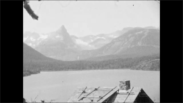 1920s: Mountain lake vista, Rocky islands in large mountain lake. Log buildings on lakeside. Man removes hat. Snow-capped mountain and valley.