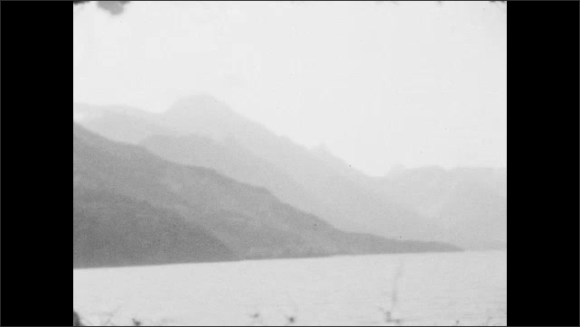 1920s: mountains with trees slope down into a lake. women with hats sit on benches in ship, talk and look at nature.