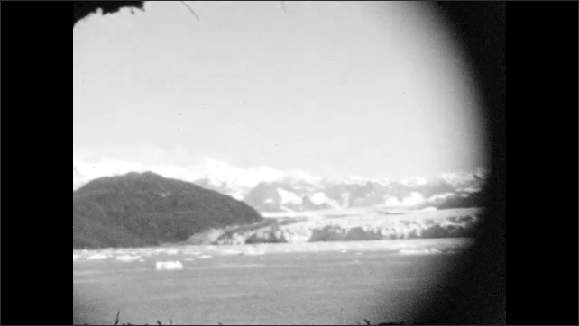 1920s: ALASKA: glacier meets water. Ice and snow by water. Ice floats in water. Mountains by lake
