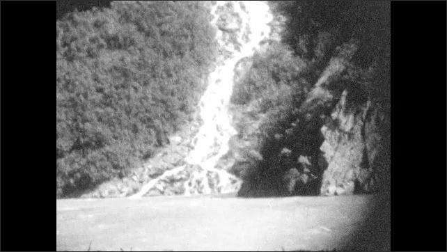 1920s: ALASKA: vehicle drives over bridge. View of car from behind. Waterfall runs down rock face.