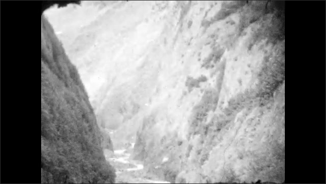 1920s: ALASKA: rapids on river. River flows through gorge. Rock face by river