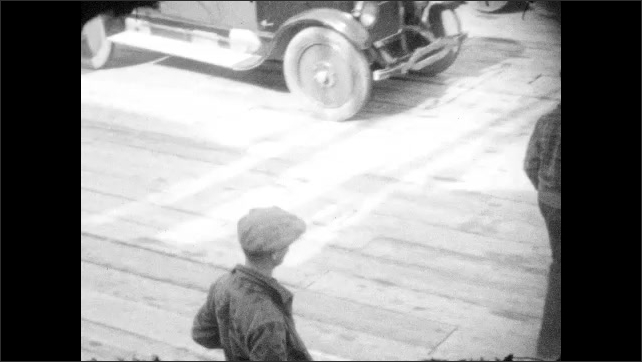 1920s: ALASKA: man in flat cap stands by car. Men smile at camera. Buildings in Prince William Sound