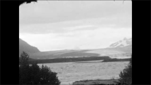 1920s: ALASKA: view of mountains and now from train. Stream by Prince William Sound. View from train