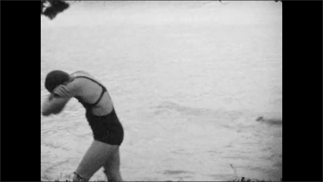 1930s: Boys and girls splash and play in lake. Boy and girl wrestle in lake.