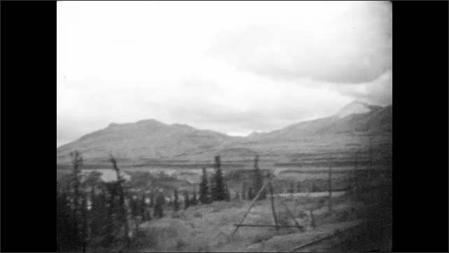 1930s: Train passes cliffs and pine forest. Train sits on tracks. Mountains and tundra valley panorama.