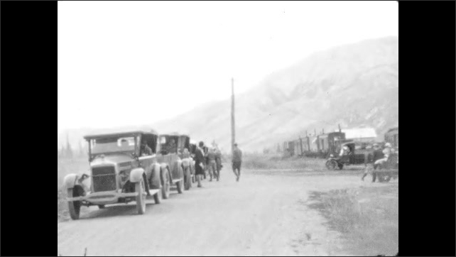 1930s: Wooden posts and location sign. People gather near parked cars on roadside. People sit in parked cars. Wooden gateway and sign.