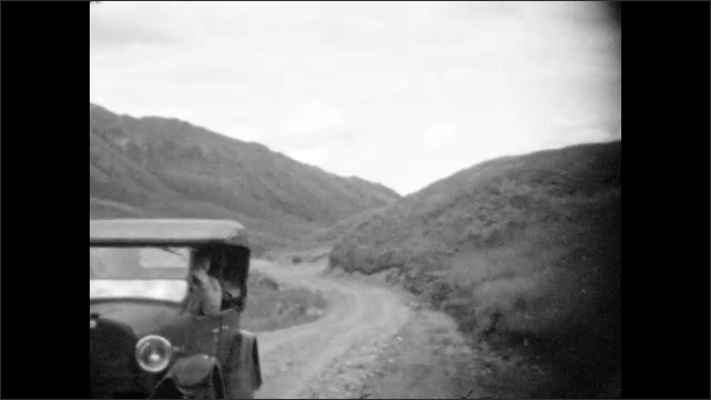 1920s: Hillsides and mountains of Alaska. Car parked on dirt road. Mountain goats graze and walk on hillside.