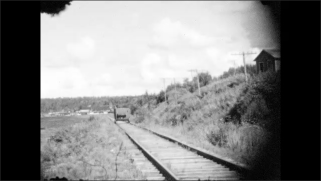 1920s: Special car travels down railway tracks. Railway track next to ocean inlet.