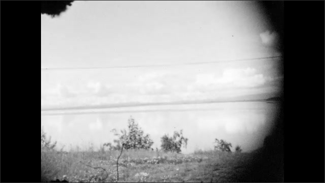 1920s: View of ocean inlet and clouds.