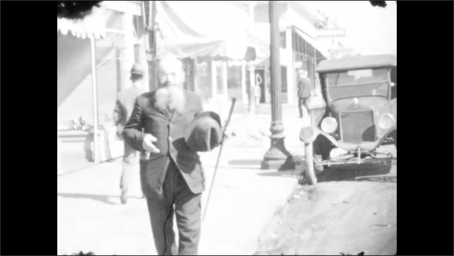 1920s: Bearded man in suit stands on city sidewalk. Bearded man removes his hat. Bearded man walks and talks passionately, waving his cane.