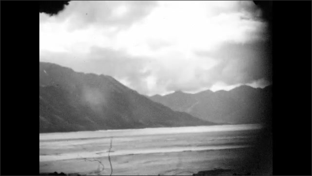 1920s: ALASKA: view across water towards mountains. Clouds over mountains and lake. Snow on mountain top.