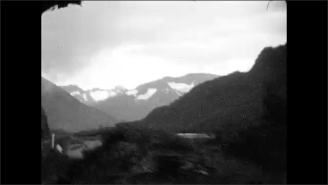 1920s: ALASKA: river runs through valley. Train tracks in mountain valley. View across river from train