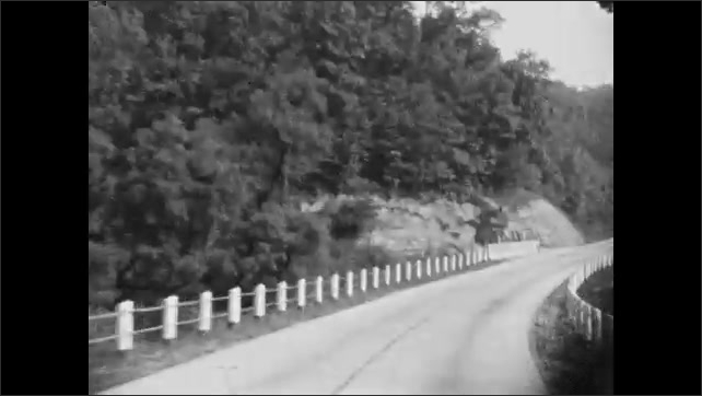 1930s: Woman and girl stand by car parked on side of road. Road sign for Ferguson's motel. Driving down road.